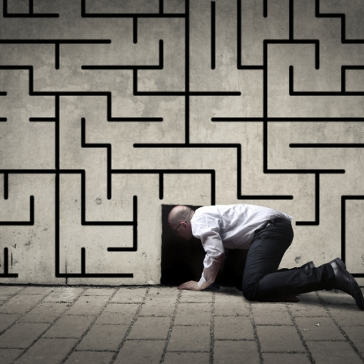 Businessman crawling into a black hole with a maze drawn on the wall